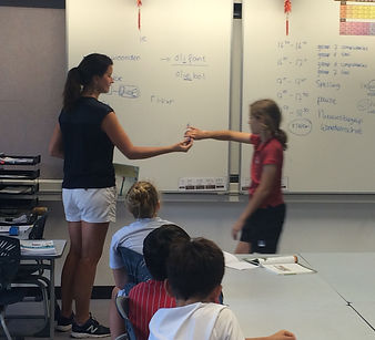 Dutch teacher giving student a marker to write on the blackboard in front of a class with students