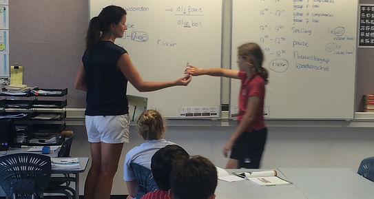 Dutch teacher in front of the classroom handing a student a marker to write on the whiteboard