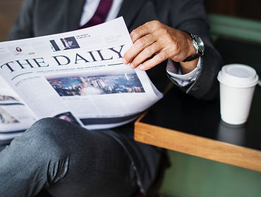 Man in suit reading The Daily Newspaper