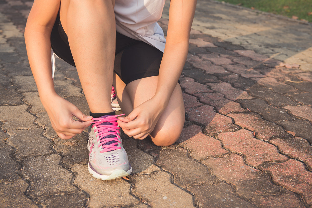 Woman lacing her running shoes before running her first mile!