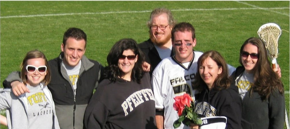 Jake and his family posing for a photo at his senior day game