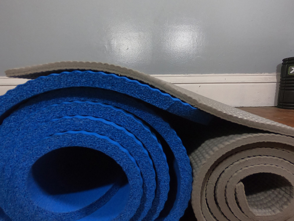 Extra thick yoga mat and a traditional yoga mat for running recovery.