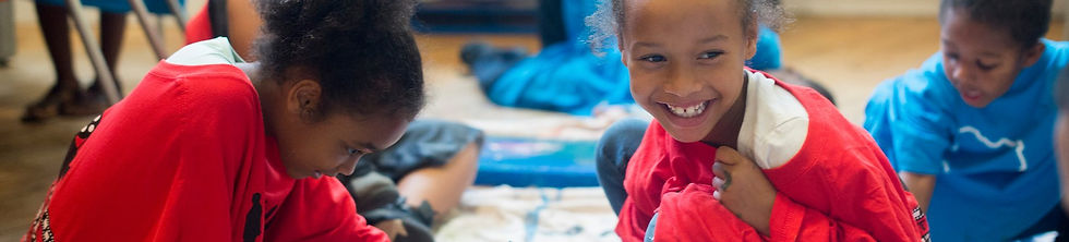 2 young girls are smiling and painting in one of the Community Art Center classrooms