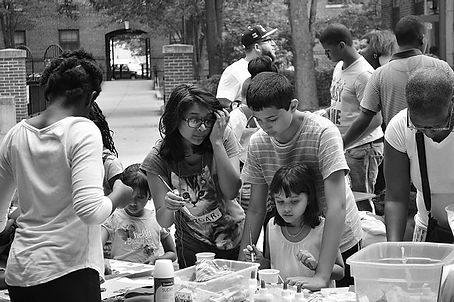 A group of young people and adults is painting and helping each other with their art outside