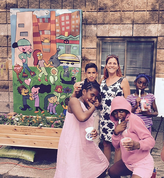 Susan Richards, president of Community Art Center board is posing with a group of young members of the Art Center