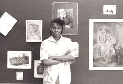 A young woman poses in front of artistic drawings