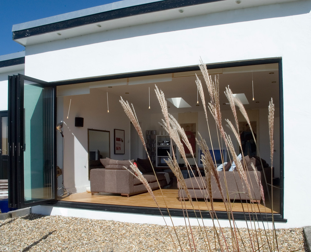 Bi-folding doors opening out from the living room to the garden from a project designed by Bliss Interiors Ltd
