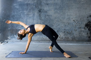 Woman practicing advanced yoga against a
