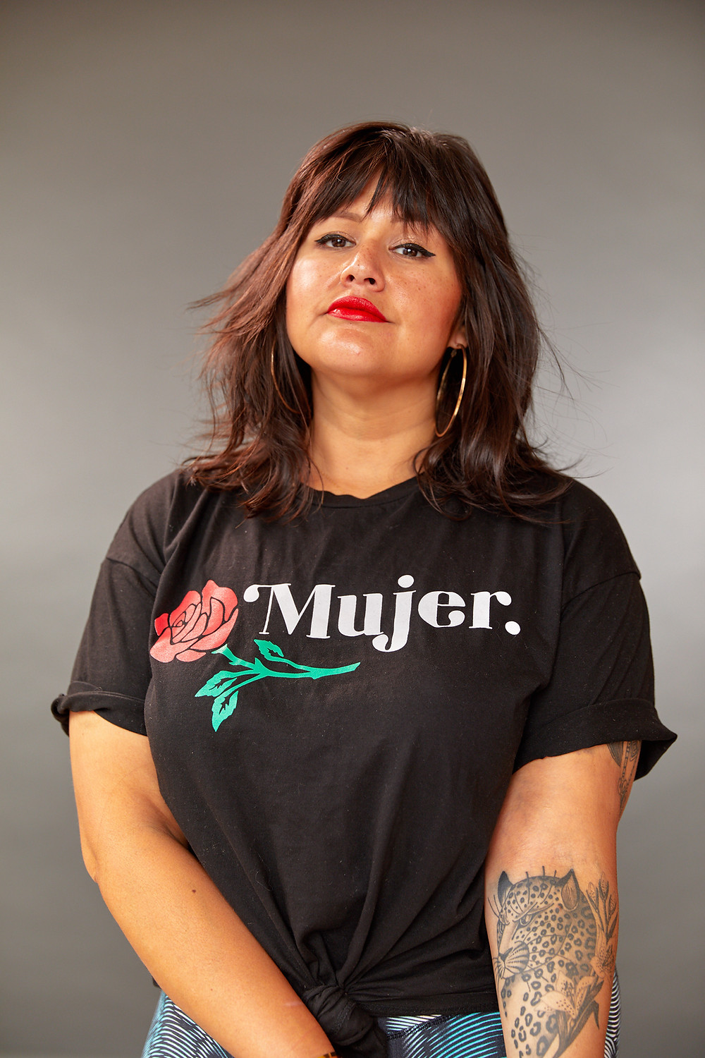 Katie stands wearing a black t-shirt that says Mujer
