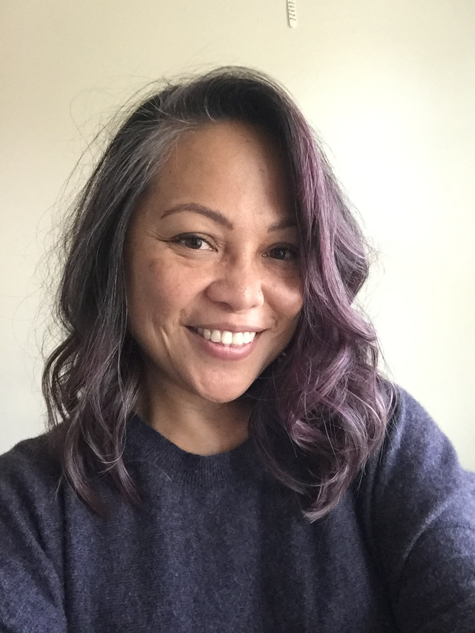 Yale is wearing a dark gray shirt with purple highlights in her hair