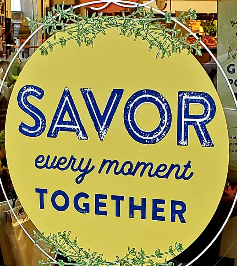 "Holiday sign reading ""Savor every moment together"""