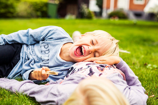 cheerful-boy-lying-on-his-sisters-stomach-in-yard-52NE8X9.jpg