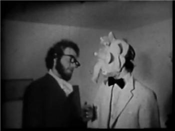L'un des deux est un monstre. Saurez-vous déterminer lequel, entre celui qui est élégamment vêtu de blanc pur, et celui qui est désinvoltement attifé de noir ? Encore une fois, tout est une histoire de masques...