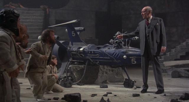 """L'Être Suprême (rôle, ici, de Ralph Richardson), sermonnant les nains à son service (la figure du nain, et plus généralement de la """"bête de foire"""" ponctue régulièrement l'OEuvre de Terry Gilliam)."""