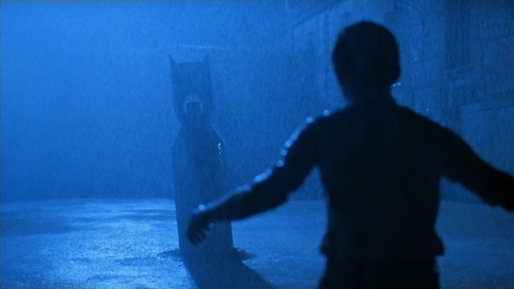 Une silhouette d'enfant, formant avec ses bras une croix, tel un crucifix, faisant face à une silhouette, voilée d'orage, dont l'ombre semble tendue vers lui, comme pour lui montrer le chemin, lui montrer le destin... La bombe serait-elle le reflet manchot, perverti, de l'enfant désarmé, sur un miroir de pluie ?