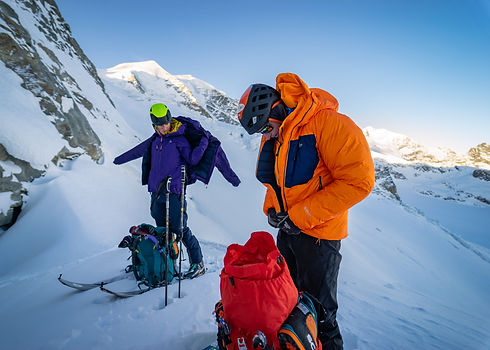 Climbers zipping up mountain equipment down jackets