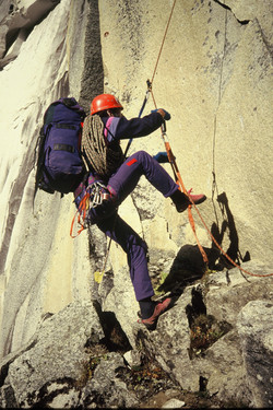 Climber with rucksack and rope on wall
