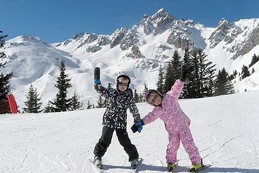 Frère et soeur en cours de ski font un grand salut à tous et à leur moniteurde ski