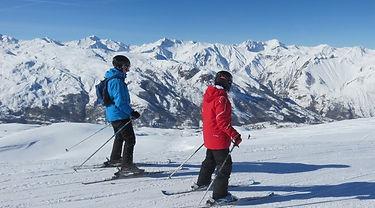 Père et fils appliquent leur leçon de ski devant un superbe panorama