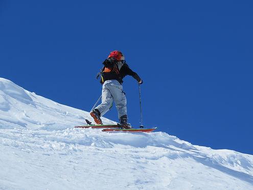 Arrivée à un col en ski de randonnée guidé par un moniteur de ski