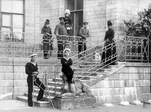 Στο παλάτι της Γκάτσινα, κατοικίας της οικογένειας του τσάρου Αλεξάνδρου Γ΄. Ο τσάρος, όρθιος ψηλά στο κέντρο, κρατάει την κόρη του Όλγα. Δεξιά του ο Νικόλαος και αριστερά του η Ξένια. Στην άκρη δεξιά, η τσαρίνα Μαρία. Στην βάση της σκάλας ο Γεώργιος και καθιστός ο Μιχαήλ.