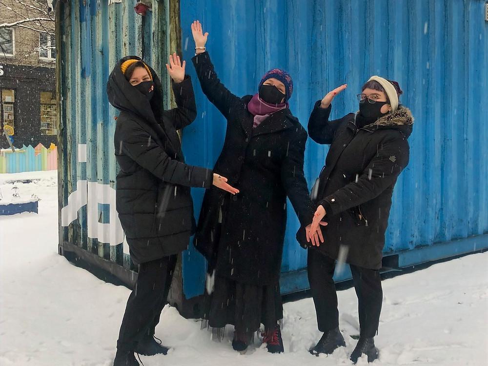 Kristiina, Epp ja Eva Marta seisavad lumisel maal IDA raadio sinise konteineri ees, käed rõõmsalt laiali, nagu esitledes Eppu kui vahvat külalist.