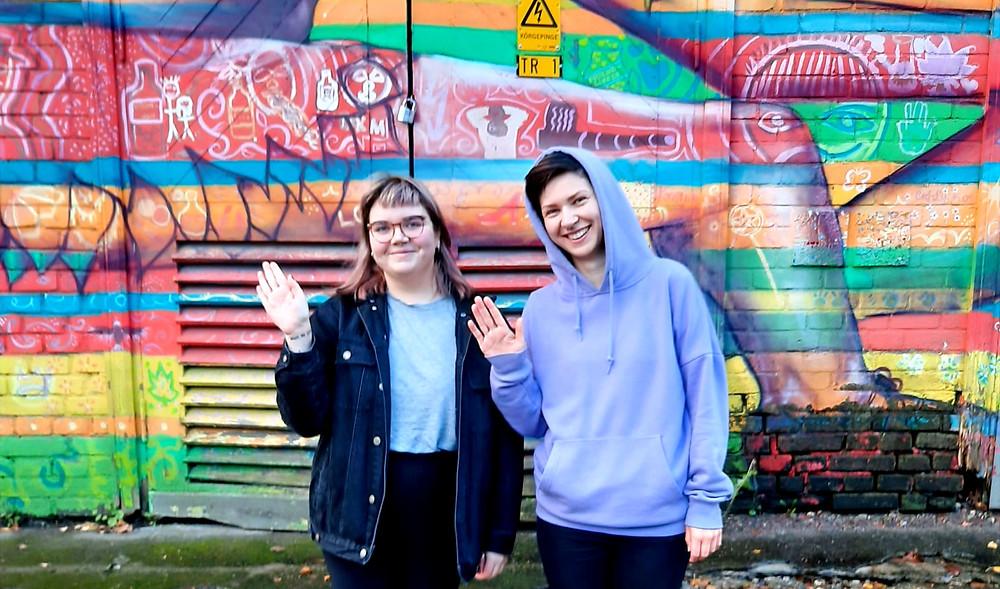 Eva Marta ja Kristiina lehvitamas värvilise seina ees enne oma esimese IDA raadio saate eetrit