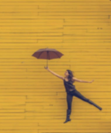 woman with umbrella in front of yellow wallpexels-photo-57851.jpeg