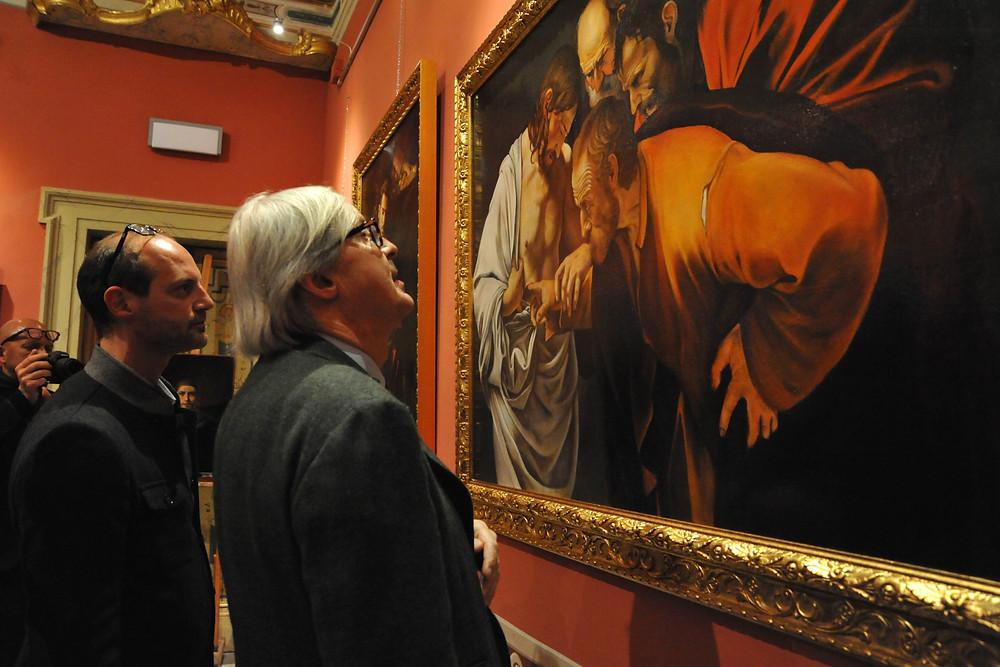 """Vittorio Sgarbi  incredulo di fronte alla copia di Tizzano dell' """"Incredulità di Tommaso"""" di Caravaggio"""