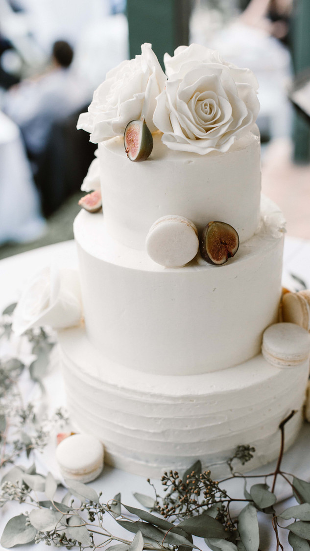Textured buttercream wedding cake with sugar flowers, macarons, and fresh figs