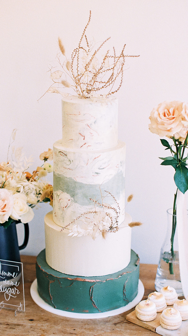 4 tier wedding cake with marbled buttercream metallic accents
