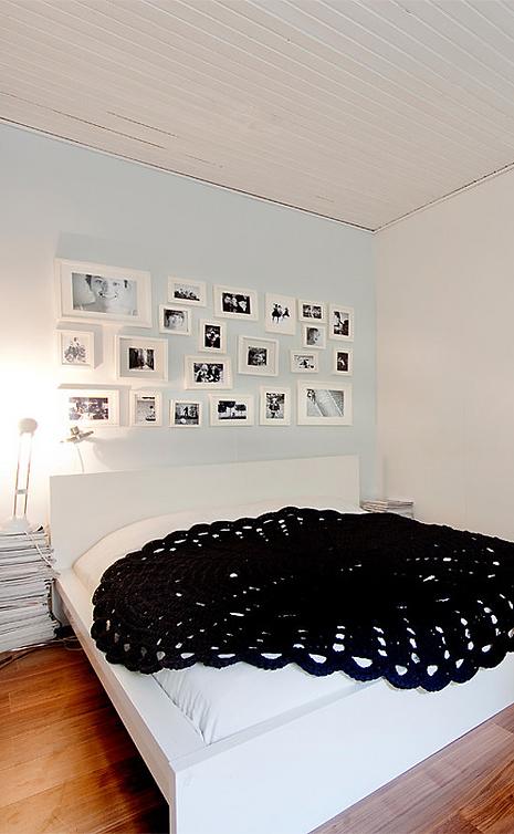 Virkkuukoukussa iso musta virkattu matto sängyllä