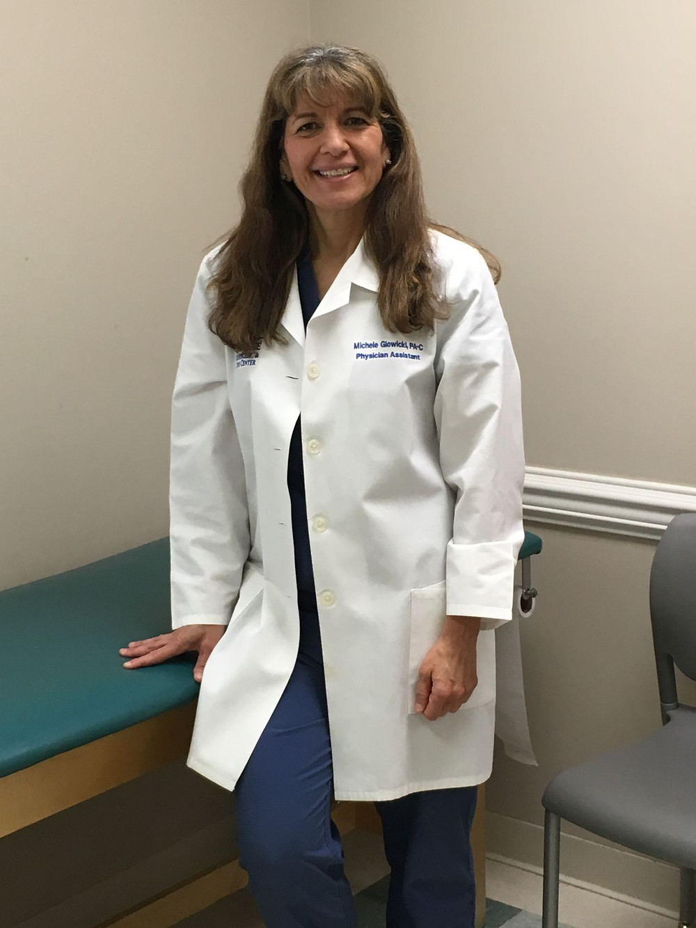 Blue Ridge Physician Assistant, Michele Glowicki, smiling and standing in front of an exam table