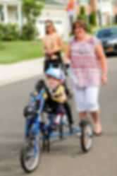 Young girl in yellow shirt riding in a handcycle with her mom behind her