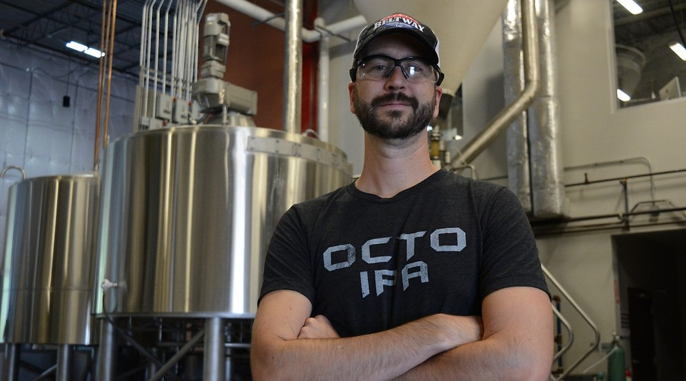 Beltway Brewing owner Sten Sellier standing in front of brewery equipment