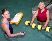 Physical therapist and patient in the pool with water weights