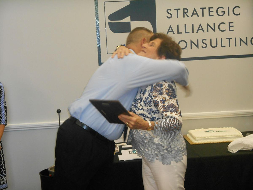 CEO of Strategic ACI hugs Mason Enterprise Center manager in thanks.