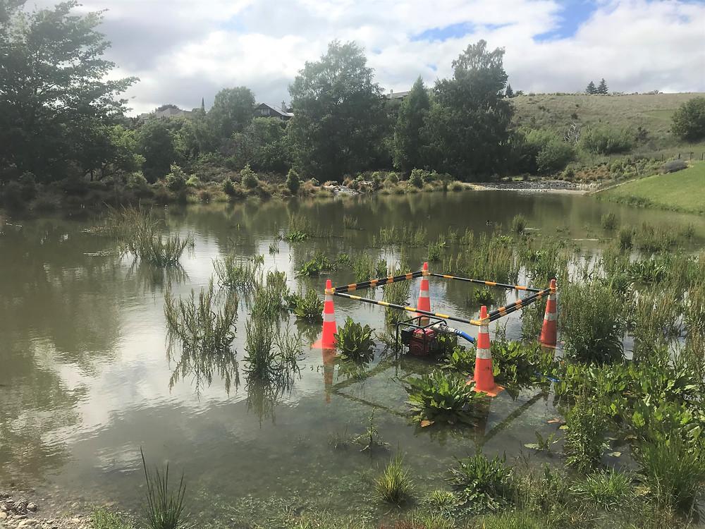 Pump in wet dry pond wide shot