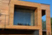 Casa in legno moderna, rivestimento in listelli in larice, frangisole