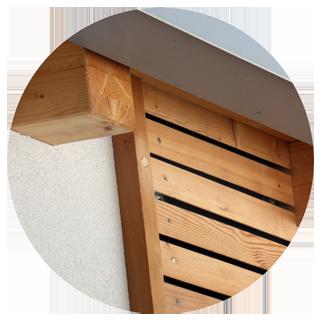 Dettaglio casa in legno. Lattoneria alluminio listelli in larice intonaco