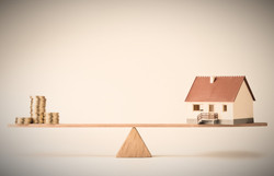 Model house and money coins balancing on