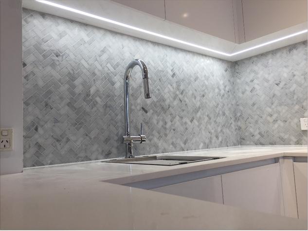 Carrara marble herringbone wiith chrome tap.