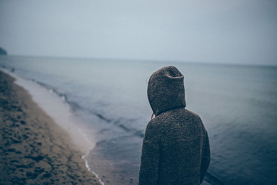Man in sweatshirt on beach