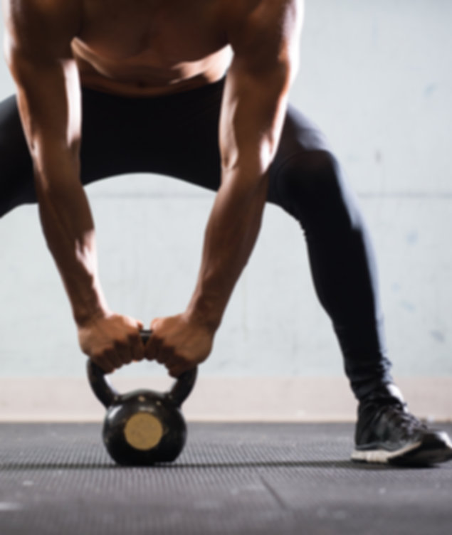 Muscular Man Lifting Kettle Ball