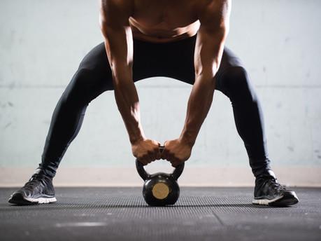 Uomo muscolare sollevamento bollitore sfera