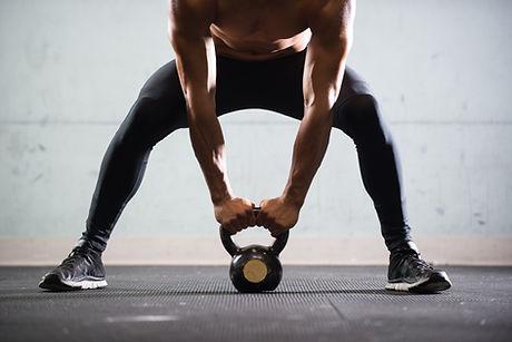 Muscular Man Lifting Kettle-Ball