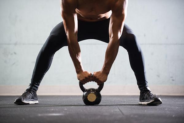 A strong man bent over lifting a kettlebell