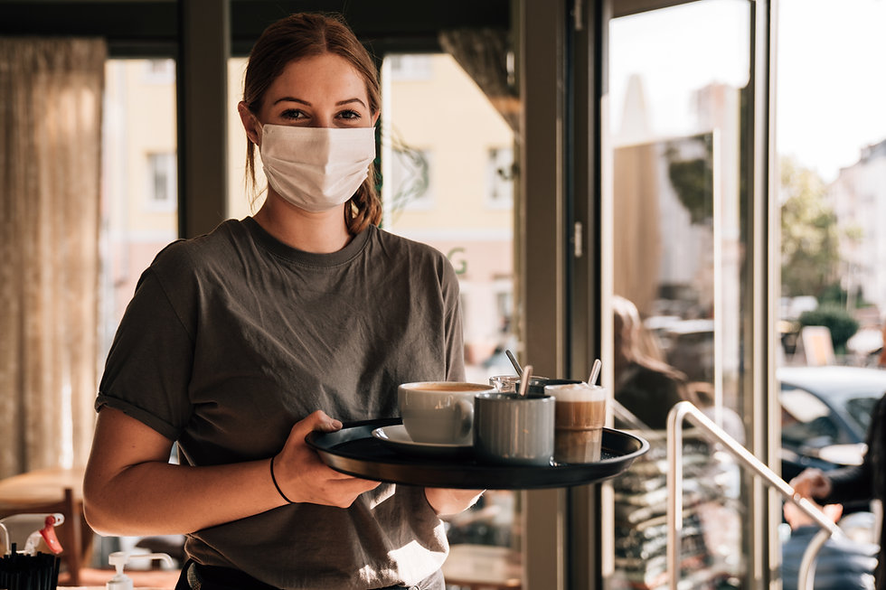 a young woman serving a cup of coffee covid-19 mask