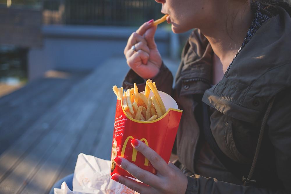 Una mujer comiendo patatas fritas.