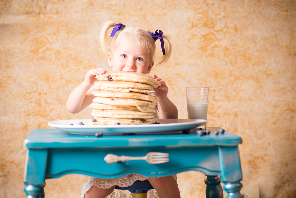 Kid eating a stack of huge pancakes